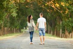 Los pares jovenes felices caminan en la carretera nacional al aire libre, concepto romántico de la gente, estación de verano fotografía de archivo libre de regalías