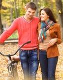 Los pares jovenes felices con la bicicleta en otoño parquean Foto de archivo