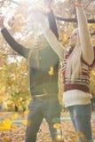 Los pares jovenes felices con los brazos aumentaron el goce de las hojas de otoño que caían en parque fotos de archivo libres de regalías
