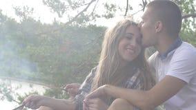 Los pares jovenes felices del adolescente frieron las salchichas en hoguera ahumada en el primer del bosque almacen de video