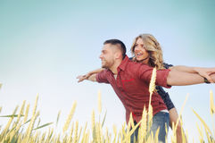 Los pares jovenes felices en amor se divierten romance y en el campo de trigo i Fotografía de archivo