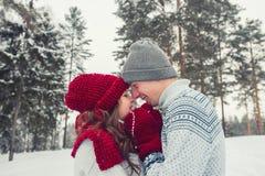Los pares jovenes felices en el amor que abraza en invierno parquean cara a cara cerca de uno a Imagen de archivo libre de regalías