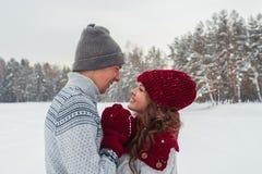 Los pares jovenes felices en el amor que abraza en invierno parquean cara a cara cerca de uno a Imágenes de archivo libres de regalías
