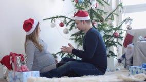 Los pares jovenes felices en el casquillo de Papá Noel se sientan en una manta cerca del árbol de navidad adornado hermoso por la
