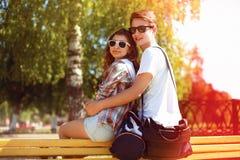 los pares jovenes felices en las gafas de sol que se sientan en el verano parquean Foto de archivo