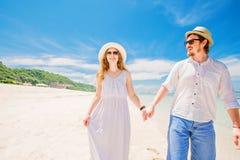 Los pares jovenes felices en sombreros y gafas de sol caminan en Imagenes de archivo