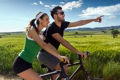 Los pares jovenes felices en una bici montan en el campo Imagen de archivo libre de regalías