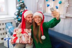 Los pares jovenes felices que sonríen, hacen el selfie, hombre que sostiene la caja de regalo en manos imagenes de archivo
