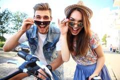 Los pares jovenes felices que van para una bici montan en un día de verano en la ciudad Se están divirtiendo junto Foto de archivo