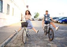 Los pares jovenes felices que van para una bici montan en un día de verano en la ciudad Se están divirtiendo junto Fotografía de archivo