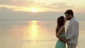Los pares jovenes felices se colocan en la playa en puesta del sol La novia besa a su novio almacen de video