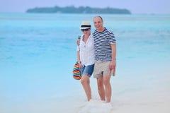 Los pares jovenes felices se divierten en la playa Foto de archivo