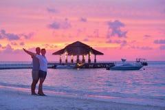 Los pares jovenes felices se divierten en la playa Foto de archivo libre de regalías