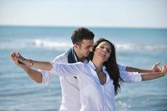 Los pares jovenes felices se divierten en la playa hermosa Imagen de archivo libre de regalías