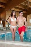 Los pares jovenes gozan de la piscina del balneario Fotos de archivo