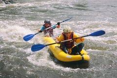 Los pares jovenes gozan del agua blanca kayaking en el r?o foto de archivo