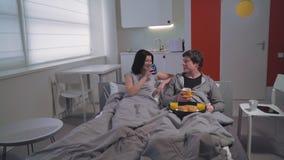Los pares jovenes gozan del desayuno romántico en cama Imagen de archivo libre de regalías