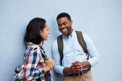 Los pares jovenes hablan inclinarse contra una pared gris Fotos de archivo libres de regalías