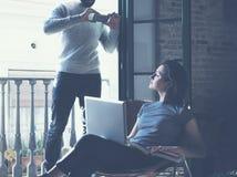 Los pares jovenes juntos vacation Hombre barbudo que hace smartphone de la foto a la muchacha hermosa Trabajo con nuevo proyecto  Imagen de archivo libre de regalías