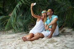 Los pares jovenes, la mujer y el hombre se sientan en la playa y tomarán los selfies vestidos en ropa brillante y en gafas de sol Imagen de archivo