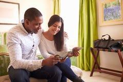 Los pares jovenes leyeron un folleto de la guía juntos en una habitación imágenes de archivo libres de regalías