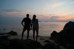 Los pares jovenes miran una disminución, el individuo con el soporte de la muchacha en la costa y la mirada en una distancia Fotografía de archivo libre de regalías
