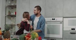 Los pares jovenes por la mañana tienen un buen humor mientras que hacen el desayuno que están bailando en una cocina moderna almacen de metraje de vídeo