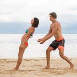 Los pares jovenes practican un ejercicio en confianza en una playa tropical Imagenes de archivo
