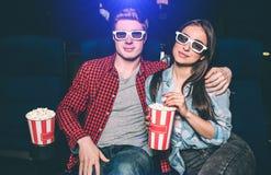Los pares jovenes preciosos se están sentando juntos en cine Él ha puesto su mano en el hombro de su novia Ella es Imagen de archivo