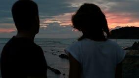 Los pares jovenes que caminan por la tarde en rocas cerca apuntalan contra una puesta del sol roja almacen de video