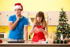 Los pares jovenes que celebran la Navidad en cocina fotos de archivo