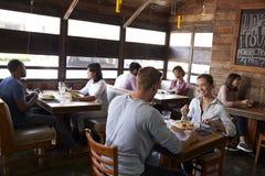 Los pares jovenes que comen el almuerzo se relajan en un restaurante Foto de archivo libre de regalías