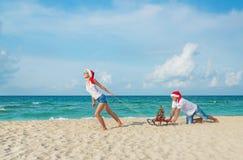 Los pares jovenes que corren en el mar varan en los sombreros de santa con el trineo y el ch Imagen de archivo