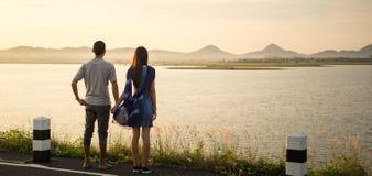 Los pares jovenes que llevan a cabo la mano y consideran paisaje hermoso foto de archivo