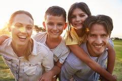 Los pares jovenes que llevan a cuestas a sus niños al aire libre miran a la cámara Foto de archivo libre de regalías
