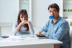 Los pares jovenes que miran a la familia financian los papeles Fotos de archivo libres de regalías