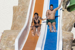Los pares jovenes que montan abajo de un diapositiva-hombre del agua que goza de un tubo del agua montan Fotos de archivo