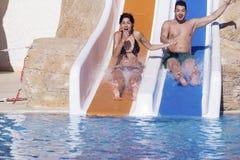 Los pares jovenes que montan abajo de un diapositiva-hombre del agua que goza de un tubo del agua montan Foto de archivo libre de regalías