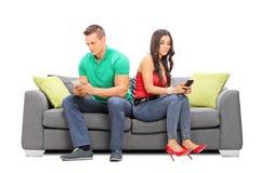 Los pares jovenes que se ignoraban asentaron en un sofá Fotografía de archivo libre de regalías