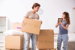 Los pares jovenes que se mueven al nuevo apartamento fotos de archivo