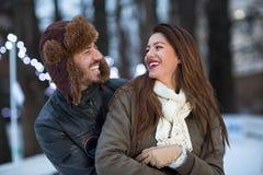 Los pares jovenes que sonríen y gozan en los momentos del invierno Imágenes de archivo libres de regalías