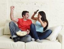 Los pares jovenes que ven la TV se divierten la celebración emocionada partido de fútbol Fotografía de archivo