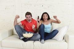 Los pares jovenes que ven la TV se divierten la celebración emocionada partido de fútbol Fotografía de archivo libre de regalías
