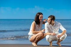 Los pares jovenes románticos dibujan formas en la arena mientras que en luna de miel Imagen de archivo libre de regalías