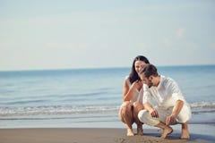 Los pares jovenes románticos drenan dimensiones de una variable del corazón en la arena mientras que en luna de miel Concepto del Fotografía de archivo