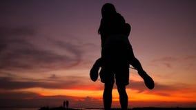 Los pares jovenes románticos siluetean el baile que hace girar alrededor en una puesta del sol asombrosa Cámara lenta de HD Phang almacen de video