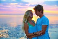 Los pares jovenes rubios abrazan en el lago del mar de la puesta del sol feliz Imagen de archivo libre de regalías