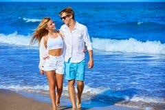 Los pares jovenes rubios que caminan en la playa apuntalan Imagen de archivo libre de regalías