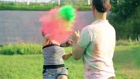 Los pares jovenes se asperjaron con la pintura seca de diversos colores almacen de metraje de vídeo