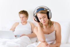 Los pares jovenes se relajan en cama con música y la computadora portátil Fotos de archivo libres de regalías